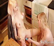 Two blondes do each other with toys at the table